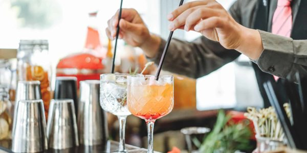 Bartender preparing different cocktails mixing with straws inside bar - Profession, work and lifestyle concept - Soft focus on top of first glass