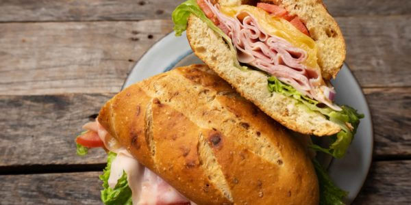 Ham and cheese sub sandwich with artisan bread on wooden background