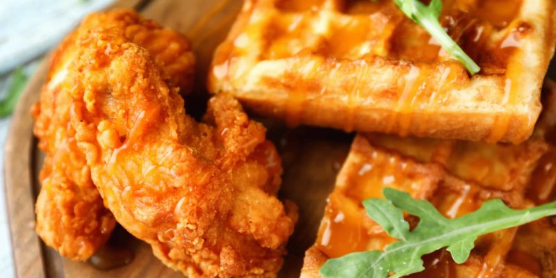 Delicious waffles with chicken and honey on wooden board, closeup